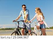 Купить «happy young couple riding bicycles at seaside», фото № 29044967, снято 23 июля 2017 г. (c) Syda Productions / Фотобанк Лори