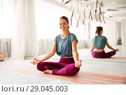 Купить «woman meditating in lotus pose at yoga studio», фото № 29045003, снято 21 июня 2018 г. (c) Syda Productions / Фотобанк Лори