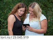 Купить «Две девушки смотрят в смартфон», фото № 29045919, снято 9 августа 2014 г. (c) Кекяляйнен Андрей / Фотобанк Лори