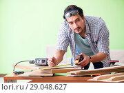 Купить «Woodworker working in his workshop», фото № 29048627, снято 15 мая 2018 г. (c) Elnur / Фотобанк Лори