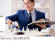 Купить «Young lawyer playing chess to train his court strategy and tacti», фото № 29049675, снято 31 июля 2018 г. (c) Elnur / Фотобанк Лори