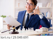 Купить «Young lawyer playing chess to train his court strategy and tacti», фото № 29049691, снято 31 июля 2018 г. (c) Elnur / Фотобанк Лори