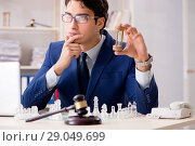 Купить «Young lawyer playing chess to train his court strategy and tacti», фото № 29049699, снято 31 июля 2018 г. (c) Elnur / Фотобанк Лори