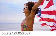 Купить «happy african woman with american flag on beach», видеоролик № 29050087, снято 24 августа 2018 г. (c) Syda Productions / Фотобанк Лори