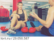 Купить «Female boxer is sitting with man and talking about healthy in gym.», фото № 29050587, снято 21 августа 2017 г. (c) Яков Филимонов / Фотобанк Лори