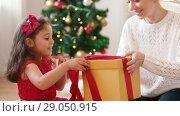 Купить «mother and daughter with christmas gift at home», видеоролик № 29050915, снято 31 августа 2018 г. (c) Syda Productions / Фотобанк Лори