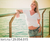 Купить «Cheerful female is posing playfully on pirce in her free time», фото № 29054015, снято 17 июля 2017 г. (c) Яков Филимонов / Фотобанк Лори