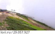 Купить «Aibga Ridge. Cable car with cabins go through the clouds. Mountains near the ski resort of Rosa Khutor in Krasnaya Polyana. Sochi», видеоролик № 29057927, снято 2 сентября 2018 г. (c) Mikhail Starodubov / Фотобанк Лори