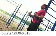 Купить «Fit Man Training Abdominal Muscles in Outdoors Gym», видеоролик № 29060515, снято 1 августа 2018 г. (c) Pavel Biryukov / Фотобанк Лори