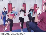 Купить «Sporty women and their trainer are doing kick in gym.», фото № 29060927, снято 8 октября 2017 г. (c) Яков Филимонов / Фотобанк Лори
