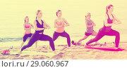Купить «attractive females exercising yoga poses on sunny beach», фото № 29060967, снято 22 мая 2017 г. (c) Яков Филимонов / Фотобанк Лори