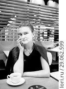 Купить «Девушка с мобильным телефоном в кафе», фото № 29062599, снято 26 августа 2018 г. (c) Victoria Demidova / Фотобанк Лори