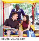 Купить «Young loving couple enjoying tour of city on trishaw with affable African American driver», фото № 29063819, снято 22 мая 2018 г. (c) Яков Филимонов / Фотобанк Лори