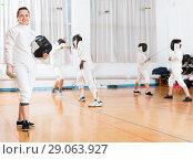 Купить «Portrait of smiling sporty young woman with foil at fencing workout», фото № 29063927, снято 30 мая 2018 г. (c) Яков Филимонов / Фотобанк Лори
