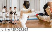 Купить «Young fencer practicing lunge with foil», фото № 29063935, снято 30 мая 2018 г. (c) Яков Филимонов / Фотобанк Лори