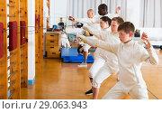 Купить «Group practicing fencing techniques in gym», фото № 29063943, снято 30 мая 2018 г. (c) Яков Филимонов / Фотобанк Лори
