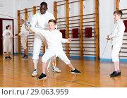 Купить «Focused boys fencers attentively listening to professional fencing coach in gym», фото № 29063959, снято 30 мая 2018 г. (c) Яков Филимонов / Фотобанк Лори