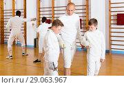 Купить «Focused boys fencers attentively listening to professional fencing coach in gym», фото № 29063967, снято 30 мая 2018 г. (c) Яков Филимонов / Фотобанк Лори