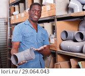 Portrait of confident African American man standing among shelves with materials for renovation works. Стоковое фото, фотограф Яков Филимонов / Фотобанк Лори