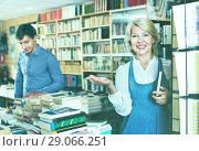 Купить «Mature smiling woman picking new book», фото № 29066251, снято 19 октября 2018 г. (c) Яков Филимонов / Фотобанк Лори