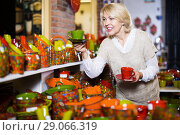 Купить «Smiling mature woman customer buying ceramic cup», фото № 29066319, снято 31 октября 2016 г. (c) Яков Филимонов / Фотобанк Лори