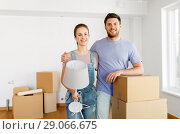 Купить «couple with boxes and lamp moving to new home», фото № 29066675, снято 4 июня 2017 г. (c) Syda Productions / Фотобанк Лори