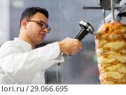 Купить «chef slicing doner meat from spit at kebab shop», фото № 29066695, снято 7 декабря 2017 г. (c) Syda Productions / Фотобанк Лори