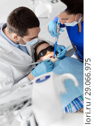 Купить «dentist treating kid teeth at dental clinic», фото № 29066975, снято 22 апреля 2018 г. (c) Syda Productions / Фотобанк Лори