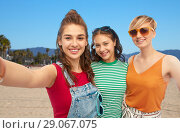 Купить «happy female friends in sunglasses taking selfie», фото № 29067075, снято 30 июня 2018 г. (c) Syda Productions / Фотобанк Лори