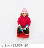 Купить «happy girl riding sled on snow in winter», фото № 29067191, снято 10 февраля 2018 г. (c) Syda Productions / Фотобанк Лори