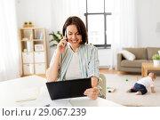 Купить «working mother with tablet pc calling on cellphone», фото № 29067239, снято 12 мая 2018 г. (c) Syda Productions / Фотобанк Лори