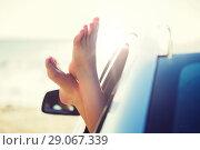 Купить «close up of woman feet showing from car window», фото № 29067339, снято 7 июня 2016 г. (c) Syda Productions / Фотобанк Лори