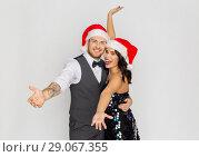 Купить «happy couple in santa hats at christmas party», фото № 29067355, снято 15 декабря 2017 г. (c) Syda Productions / Фотобанк Лори