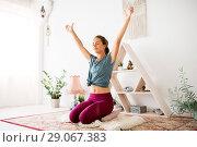 Купить «woman meditating at yoga studio», фото № 29067383, снято 21 июня 2018 г. (c) Syda Productions / Фотобанк Лори