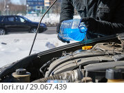 Купить «Man filling a windshield washer tank of a car by antifreeze on winter Moscow street», фото № 29067439, снято 18 марта 2018 г. (c) Георгий Дзюра / Фотобанк Лори