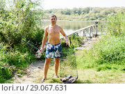 Купить «Мужчина держит в руках садок с крупной рыбой и удочку на фоне реки», эксклюзивное фото № 29067631, снято 6 сентября 2018 г. (c) Игорь Низов / Фотобанк Лори