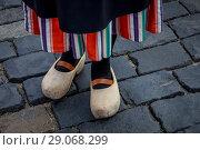 Купить «Девушка в традиционной голландской одежде и деревянных башмаках (кломпах) стоит на булыжной мостовой в центре европейского города», фото № 29068299, снято 2 сентября 2018 г. (c) Николай Винокуров / Фотобанк Лори