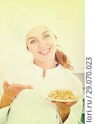 Купить «Girl cook shows plate of porrige», фото № 29070023, снято 11 декабря 2018 г. (c) Яков Филимонов / Фотобанк Лори