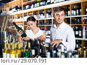 Купить «Laughing young couple choosing together wine», фото № 29070191, снято 19 декабря 2018 г. (c) Яков Филимонов / Фотобанк Лори
