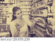 Купить «Portrait of young cheerful woman choosing paint color in jar», фото № 29070239, снято 23 февраля 2019 г. (c) Яков Филимонов / Фотобанк Лори