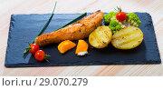 Купить «Fried salmon steak with baked potatoes, egg yolk, vegetables», фото № 29070279, снято 22 октября 2018 г. (c) Яков Филимонов / Фотобанк Лори