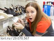Купить «Женщина шокирована ценой на обувь в магазине, держит в руках магазинный ценник», фото № 29070567, снято 14 февраля 2014 г. (c) Кекяляйнен Андрей / Фотобанк Лори