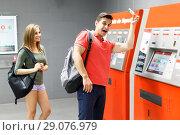 Купить «Man with his girlfriend are buy tickets and traveling», фото № 29076979, снято 14 июня 2018 г. (c) Яков Филимонов / Фотобанк Лори