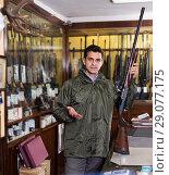 Купить «Modern male hunter choosing shotgun in store», фото № 29077175, снято 11 декабря 2017 г. (c) Яков Филимонов / Фотобанк Лори