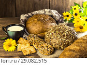 Купить «Food. Rustic still life. Assortment of fresh bread baked in a bakery, biscuits and a mug with milk on a wooden table background», фото № 29082515, снято 25 августа 2018 г. (c) Светлана Евграфова / Фотобанк Лори