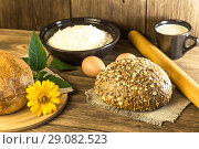 Food, breakfast. Rustic still life. Fresh bread baked in the bakery, chicken eggs, cottage cheese and milk on the background of the texture of a wooden table. Стоковое фото, фотограф Светлана Евграфова / Фотобанк Лори