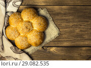 Купить «Background with food. Baking bread. Fresh baked bun with sesame seeds on the background of the texture of a wooden table», фото № 29082535, снято 25 августа 2018 г. (c) Светлана Евграфова / Фотобанк Лори