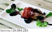 Купить «Image of baked in bacon quail with balsamic sauce on the plate indoors.», видеоролик № 29084283, снято 27 августа 2018 г. (c) Яков Филимонов / Фотобанк Лори