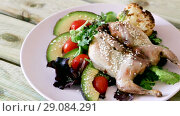 Купить «Image of quail-tobacco with sesame which served with salad of avocado and greenery on the plate indoors.», видеоролик № 29084291, снято 27 августа 2018 г. (c) Яков Филимонов / Фотобанк Лори