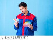 Купить «Young man contractor choosing color from rainbow», фото № 29087811, снято 3 мая 2018 г. (c) Elnur / Фотобанк Лори